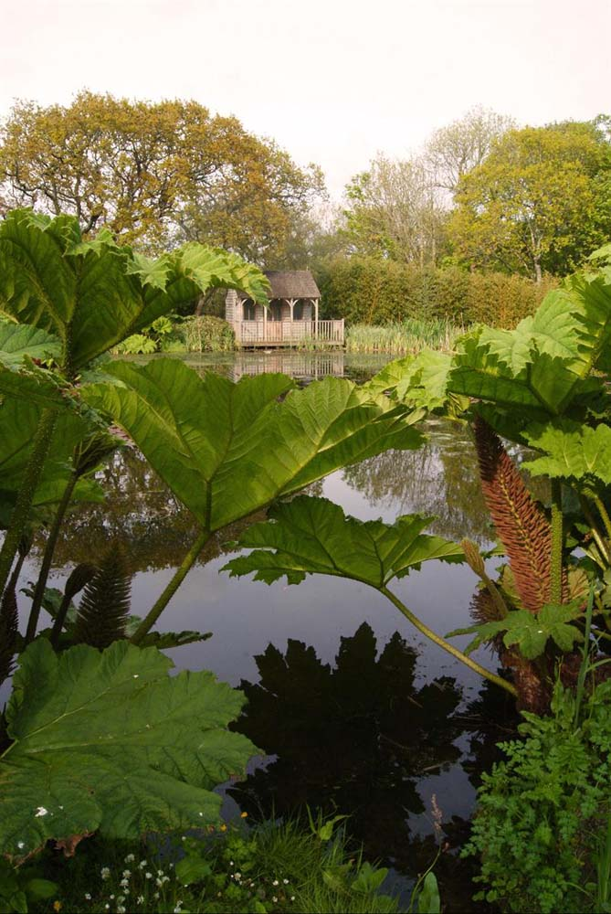 View of a summerhouse sat at the edge of the large pond through the canopy of leaves