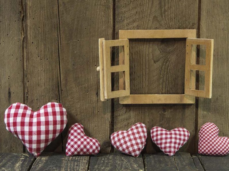 Cushioned hearts sat against a wooden wall with wooden window frame
