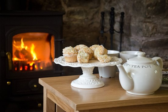 Tea and cake in front of a lit fire