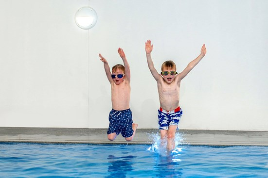 Children jumping into indoor swimming pool