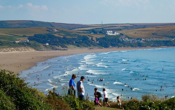 People walking on the South West Coast Path with Woolacombe Bay in the background