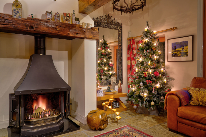 Real fire and christmas tree in a luxury cottage