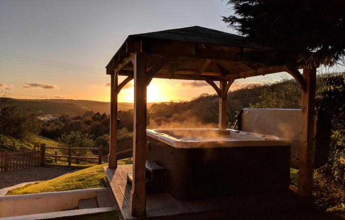 Private hot tub under a gazebo with the sun setting in the background
