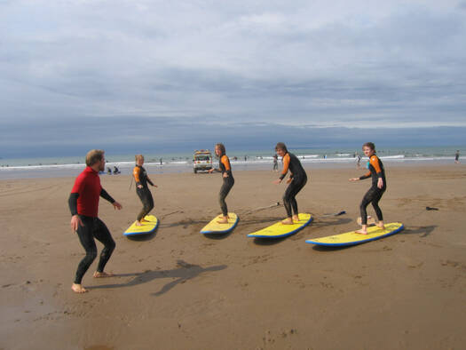 Group of teenagers being taught how to surf