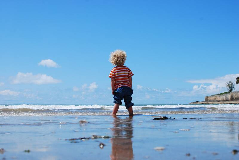 Male child with curly blonde hair standing by the sea