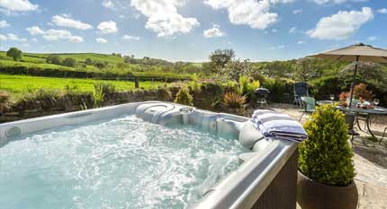 A large hot tub in a beautiful garden with plenty of jets, from one of our holiday cottages with hot tubs in the UK.